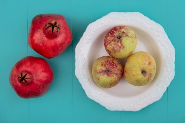 Draufsicht von frischen äpfeln auf einer schüssel mit granatäpfeln lokalisiert auf einem blauen hintergrund