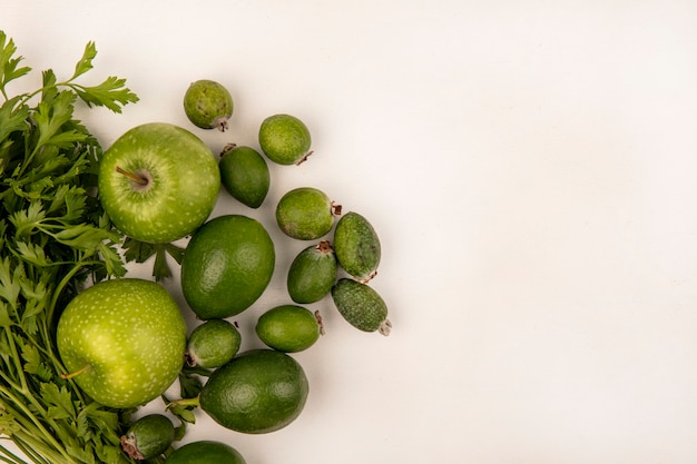 Draufsicht von frischen äpfeln mit limettenfeijoas und petersilie lokalisiert auf einer weißen wand mit kopienraum