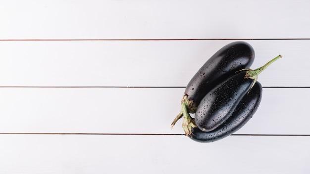 Draufsicht von frischen auberginen auf hölzerner planke