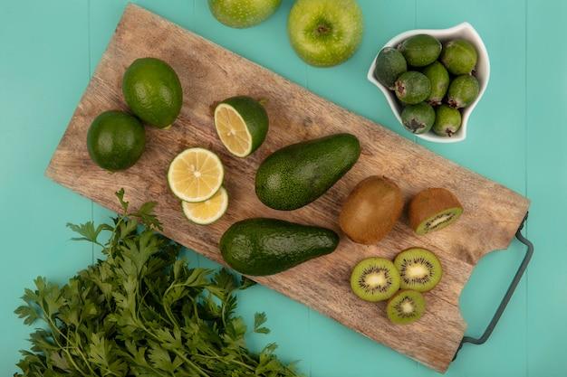 Draufsicht von frischen avocados mit limetten und kiwis auf einem hölzernen küchenbrett mit feijoas auf einer schüssel mit äpfeln und petersilie lokalisiert auf einer blauen wand