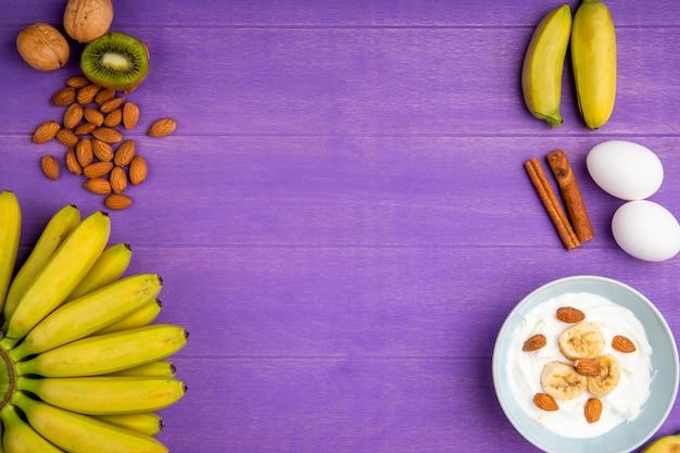 Draufsicht von frischen bananen, zimtstangen, mandel, zwei eiern und einer schüssel mit joghurt und geschnittenen bananen auf lila holz mit kopienraum