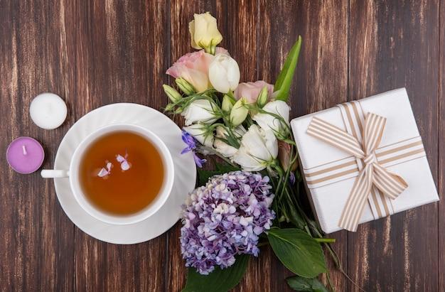 Draufsicht von frischen blumen wie gardenzia tulpenrosen mit einer tasse tee mit geschenkbox lokalisiert auf einem hölzernen hintergrund