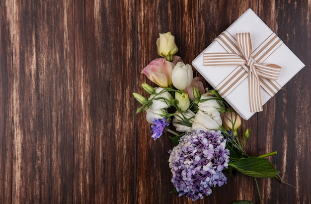 Draufsicht von frischen blumen wie gardenzia tulpenrosen mit geschenkbox lokalisiert auf einem hölzernen hintergrund mit kopienraum