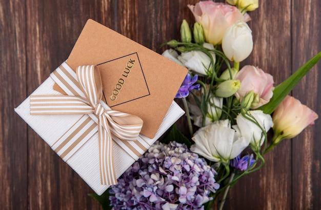 Draufsicht von frischen blumen wie gardenzia tulpenrosen mit geschenkbox lokalisiert auf einem hölzernen hintergrund