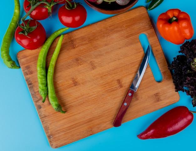 Draufsicht von frischen chilischoten auf einem holzschneidebrett mit küchenmesser und reifen tomaten auf blau
