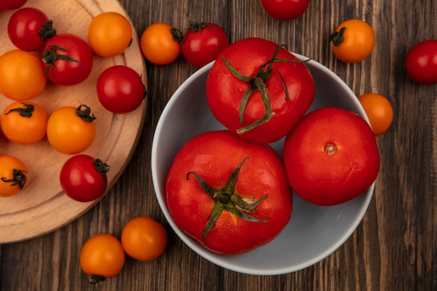 Draufsicht von frischen drei großen roten tomaten auf einer schüssel mit kirschtomaten lokalisiert auf einem hölzernen küchenbrett auf einer hölzernen oberfläche