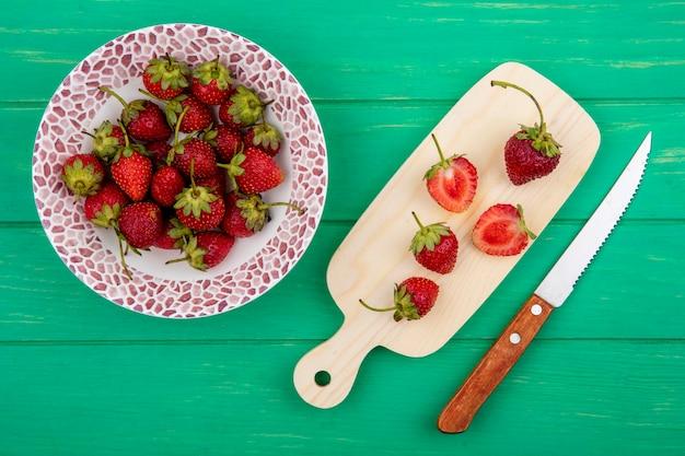 Draufsicht von frischen erdbeeren auf einer schüssel mit scheiben von erdbeeren auf einem hölzernen küchenbrett mit einem messer auf einem grünen hölzernen hintergrund