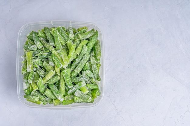 Draufsicht von frischen frostigen grünen bohnen, die mit frost im plastik coserntainer auf betontisch bedeckt sind
