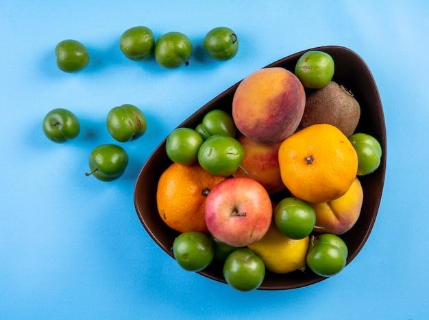 Draufsicht von frischen früchten pfirsich apfel-kiwi und grünen sauerkirschpflaumen in einer schwarzen schüssel auf blau