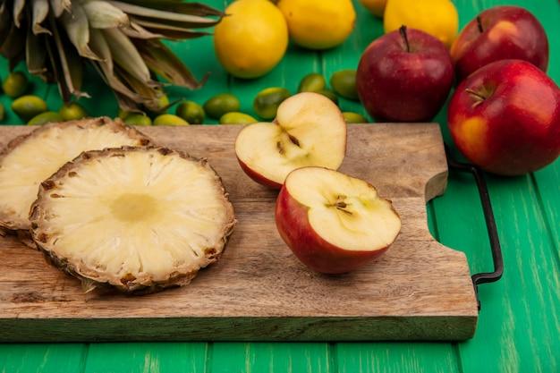 Draufsicht von frischen früchten wie äpfeln und ananas lokalisiert auf einem hölzernen küchenbrett mit roten äpfeln und zitronen von kinkans lokalisiert auf einem grünen hölzernen hintergrund