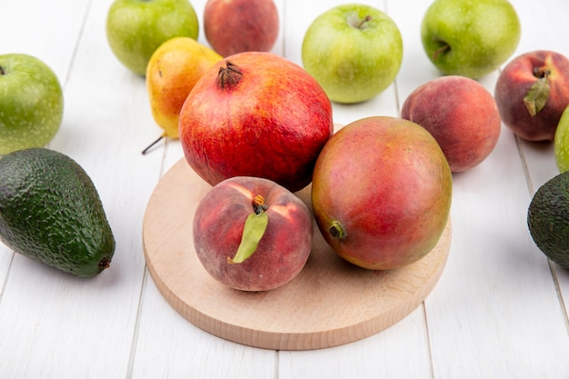 Draufsicht von frischen früchten wie granatapfel-pfirsich-mango auf holzküchenbrett mit apfel-birnen-pfirsichen isoliert auf weiß