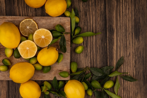 Draufsicht von frischen früchten wie kinkans und zitronen lokalisiert auf einem hölzernen küchenbrett auf einer holzwand mit kopierraum