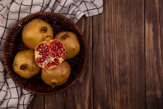 Draufsicht von frischen ganzen und halben granatäpfeln auf einem eimer auf einem karierten tuch auf einer holzoberfläche mit kopierraum