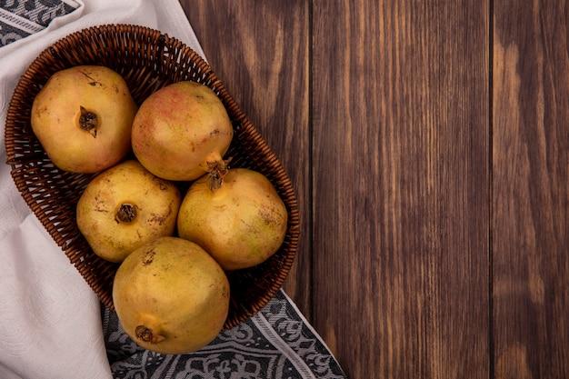 Draufsicht von frischen gelben granatäpfeln auf einem eimer auf einem stoff auf einem hölzernen hintergrund mit kopienraum