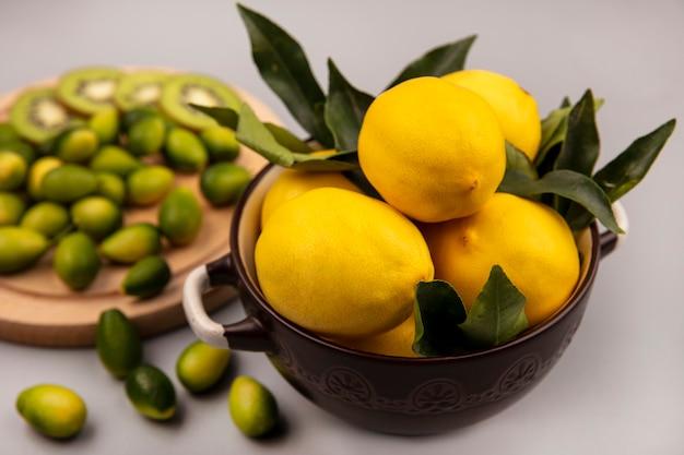 Draufsicht von frischen gelben zitronen auf einer schüssel mit kinkans und kiwischeiben auf einem hölzernen küchenbrett auf einer weißen wand