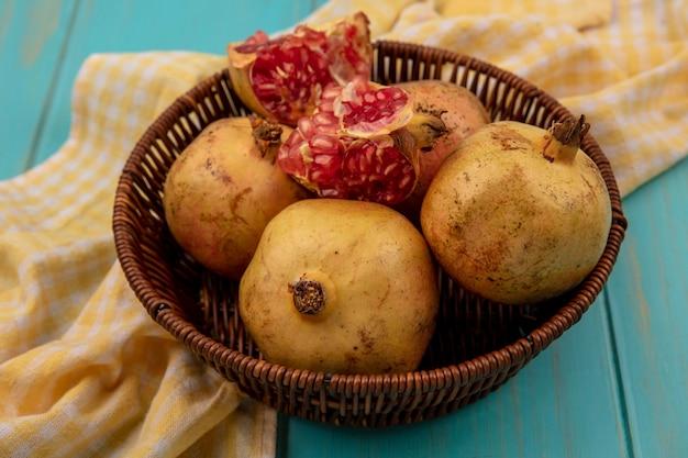 Draufsicht von frischen granatäpfeln auf einem eimer auf einem gelben karierten tuch auf einer blauen holzoberfläche