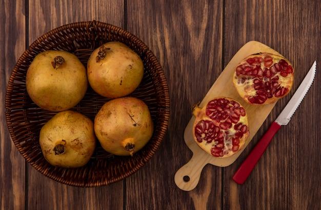 Draufsicht von frischen granatäpfeln auf einem eimer mit halbierten granatäpfeln auf einem hölzernen küchenbrett mit messer auf einer holzwand