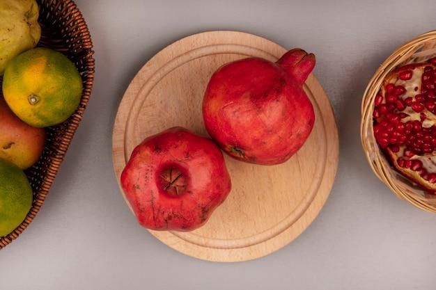 Draufsicht von frischen granatäpfeln auf einem hölzernen küchenbrett mit mandarinen auf einem eimer