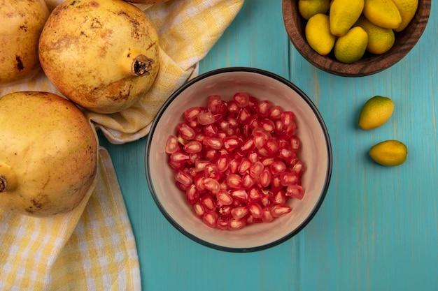 Draufsicht von frischen granatapfelkernen auf einer schüssel mit granatäpfeln lokalisiert auf einem gelben karierten tuch mit kinkans auf einer holzschale auf einem blauen hölzernen hintergrund