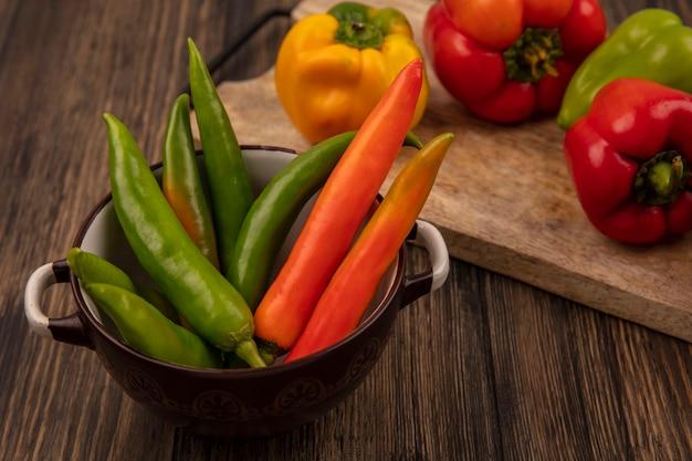 Draufsicht von frischen grünen und orange paprika auf einer schüssel mit gelben roten und grünen paprika auf einem hölzernen küchenbrett auf einer hölzernen oberfläche