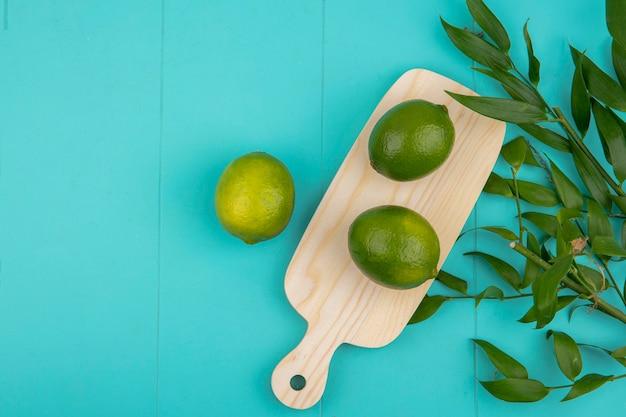 Draufsicht von frischen grünen zitronen auf holzküchenbrett mit blättern auf blau mit kopienraum