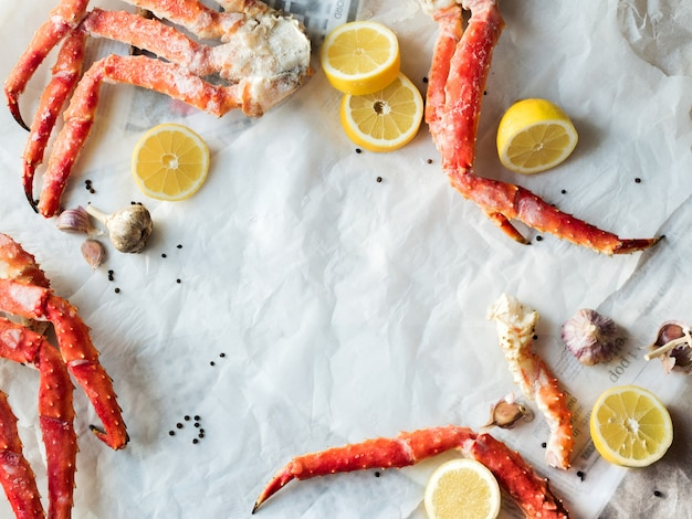 Draufsicht von frischen krabbenhalsfrüchten mit zitrone und gewürzen auf zerknittertem papier.