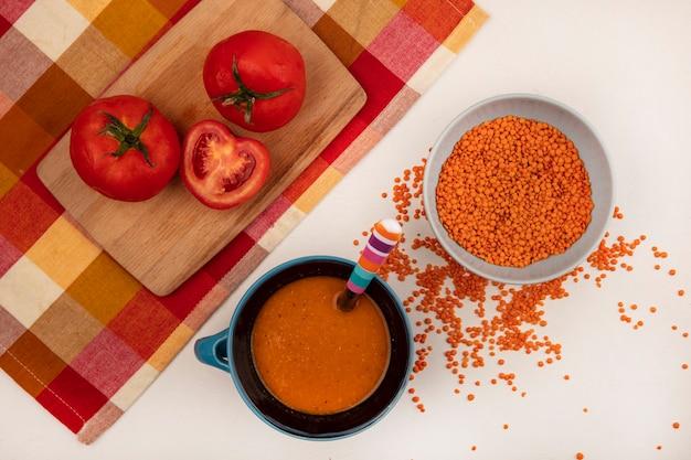 Draufsicht von frischen linsen auf einer schüssel mit orangenlinsensuppe auf einer schüssel mit tomaten auf einem hölzernen küchenbrett auf einem karierten tuch auf einem weißen hintergrund