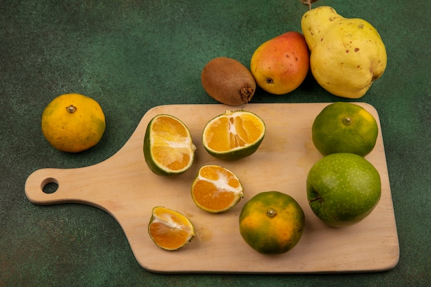 Draufsicht von frischen mandarinen auf einem hölzernen küchenbrett mit mandarinenquitte und birne lokalisiert