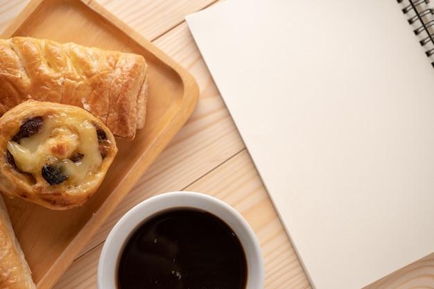 Draufsicht von frischen nachtischen und von torten, von leerem notizbuch und von weißen kaffeetassen.