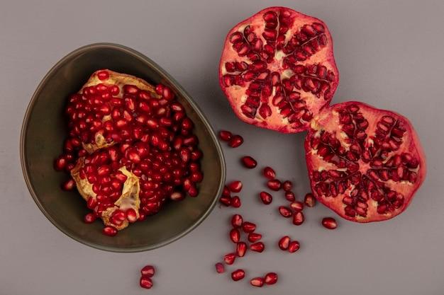 Draufsicht von frischen offenen granatäpfeln auf einer schüssel mit halbierten granatäpfeln isoliert