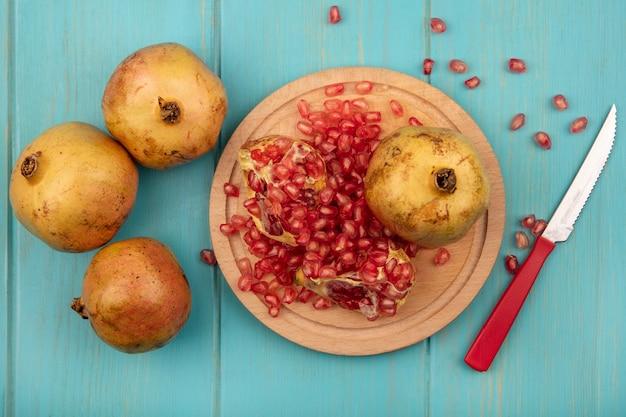 Draufsicht von frischen offenen granatäpfeln mit samen lokalisiert auf einem hölzernen küchenbrett mit messer auf einer blauen holzoberfläche