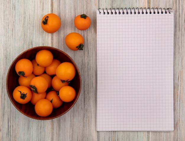 Draufsicht von frischen orangenkirschtomaten auf einer holzschale auf einer grauen holzoberfläche mit kopienraum