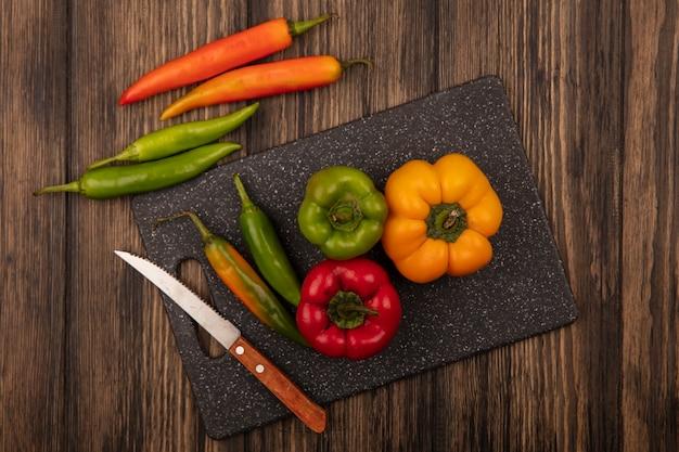 Draufsicht von frischen paprikaschoten auf einem schwarzen küchenbrett mit messer mit paprikaschoten lokalisiert auf einer holzwand