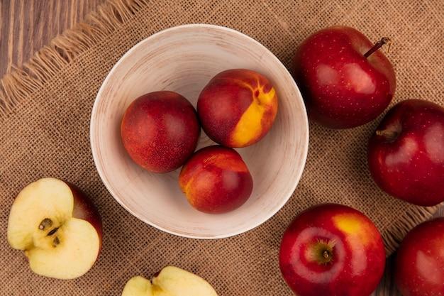 Draufsicht von frischen pfirsichen auf einer schüssel auf einem sack tuch mit äpfeln lokalisiert auf einem hölzernen hintergrund