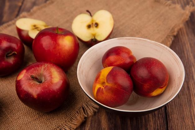 Draufsicht von frischen pfirsichen auf einer schüssel mit äpfeln lokalisiert auf einem sack stoff auf einer holzwand