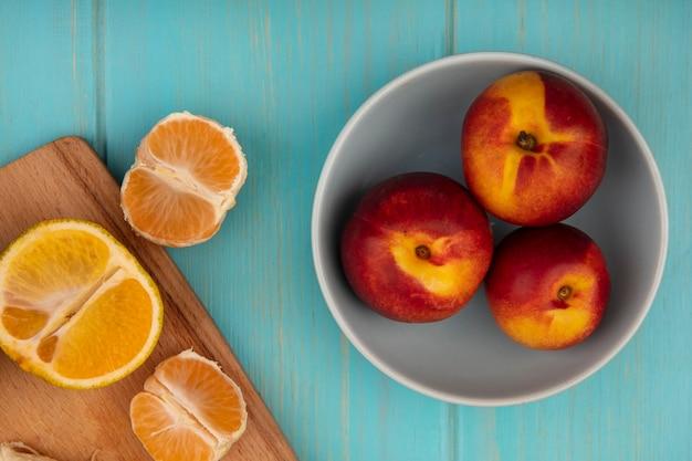 Draufsicht von frischen pfirsichen auf einer schüssel mit mandarinen auf einem hölzernen küchenbrett auf einer blauen holzwand