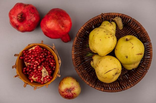 Draufsicht von frischen quitten auf einem eimer mit granatapfelkernen auf einer schüssel mit ganzem granatapfel isoliert