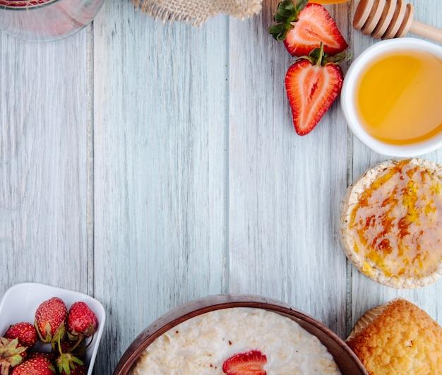 Draufsicht von frischen reifen erdbeerenhonig-haferflockenbrei und reiskuchen auf weißem holz mit kopienraum