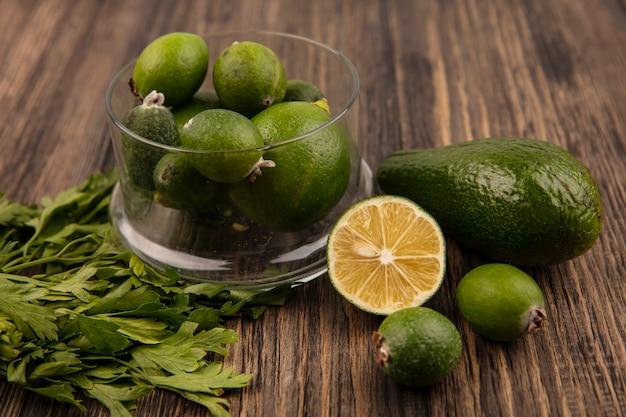 Draufsicht von frischen reifen feijoas auf einer glasschale mit avocado-halbkalk-feijoas und petersilie, die auf einer holzoberfläche isoliert werden