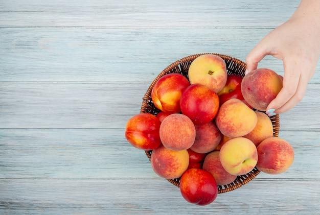 Draufsicht von frischen reifen nektarinen und pfirsichen in einem weidenkorb auf weißem hintergrund mit kopienraum