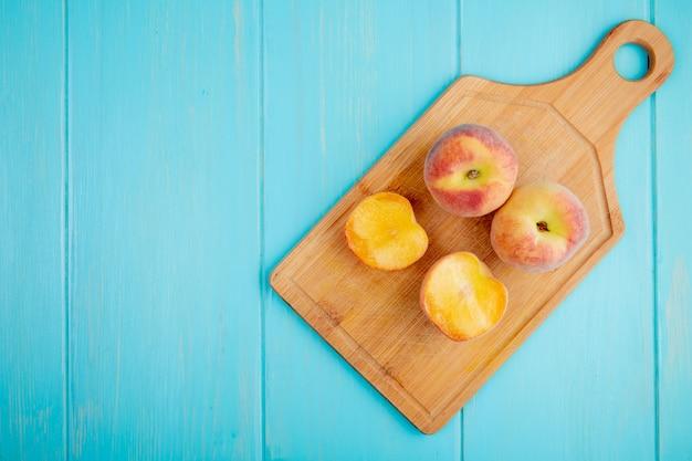 Draufsicht von frischen reifen pfirsichen auf einem holzschneidebrett auf blau mit kopienraum