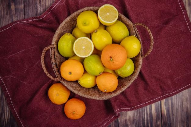 Draufsicht von frischen reifen zitronen und orangen in einem weidenkorb auf dunkelrotem stoff auf rustikalem