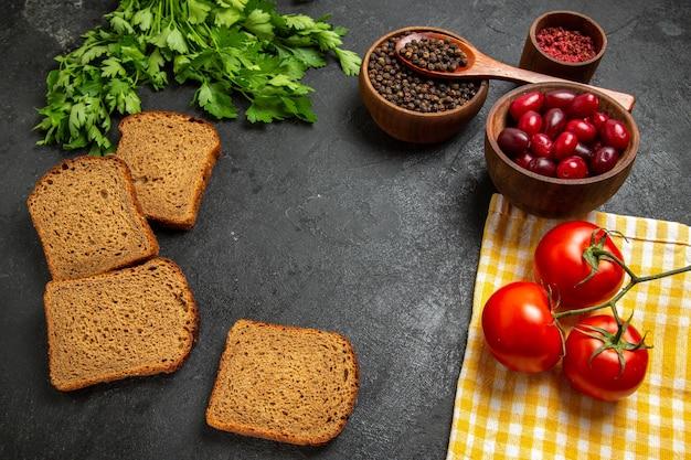 Draufsicht von frischen roten hartriegeln mit dunklem brotlaibgrün und von tomaten auf grauer oberfläche