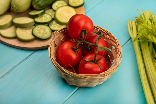 Draufsicht von frischen roten tomaten auf einem eimer mit gehackten gurken und zucchini auf einem hölzernen küchenbrett mit sellerie lokalisiert auf einer blauen holzoberfläche