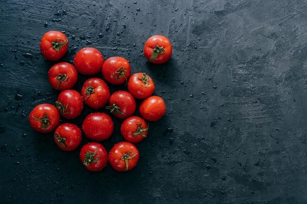 Draufsicht von frischen roten tomaten machte nach regen nass.
