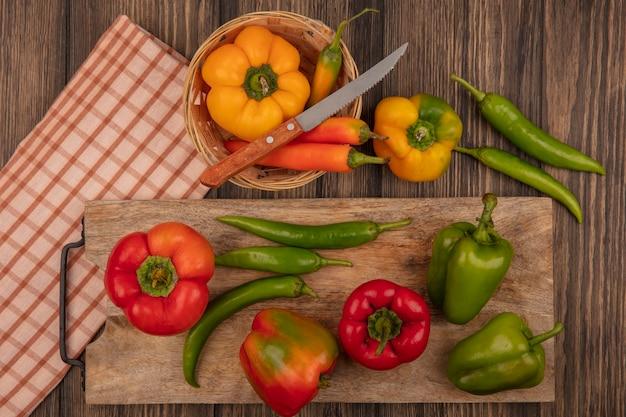 Draufsicht von frischen roten und grünen paprikaschoten auf einem hölzernen küchenbrett mit gelben paprikaschoten auf einem eimer mit messer auf einem karierten tuch auf einer holzwand