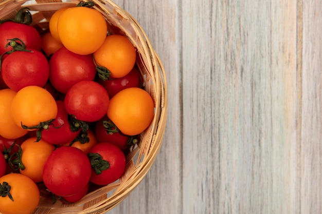 Draufsicht von frischen roten und orange tomaten auf einem eimer auf einer grauen holzoberfläche mit kopierraum