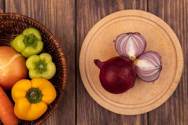Draufsicht von frischen roten zwiebeln auf einem hölzernen küchenbrett mit paprika und weißer zwiebel auf einem eimer auf einer holzwand