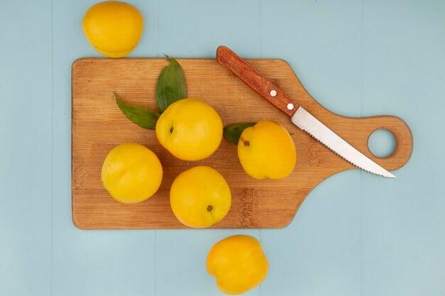 Draufsicht von frischen saftigen und gelben pfirsichen auf einem hölzernen küchenbrett mit messer auf blauem hintergrund