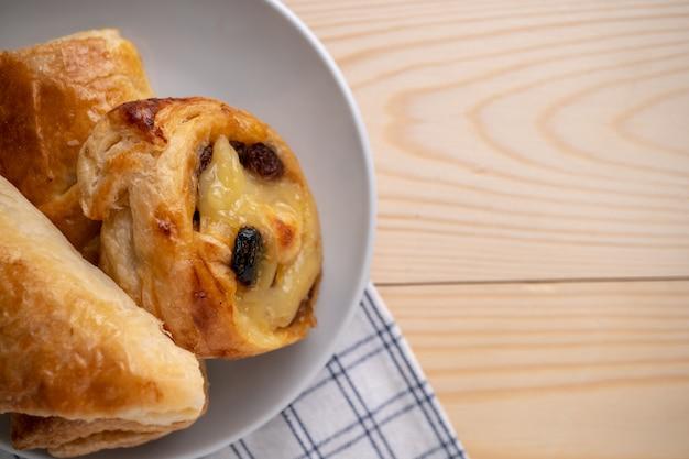 Draufsicht von frischen süßen brötchen und von torte gesetzt auf einen hölzernen behälter und eine serviette zum morgenfrühstück.